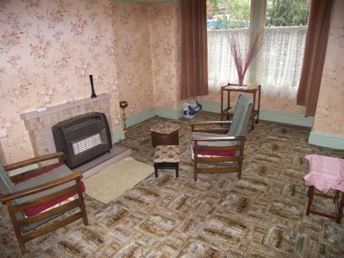 הסלון, לפני. שטיח מחריד, טפט מזעזע, תנור גז.